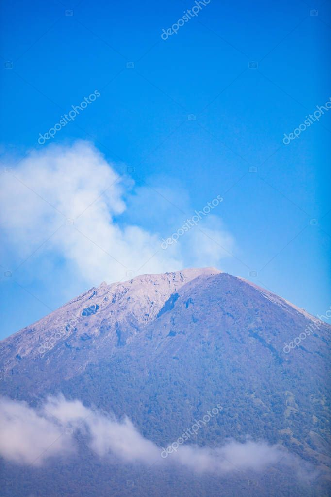 Mount Agung with smoke from the crater and clouds beneath, july 2018, couple of weeks after last eruption with lava.