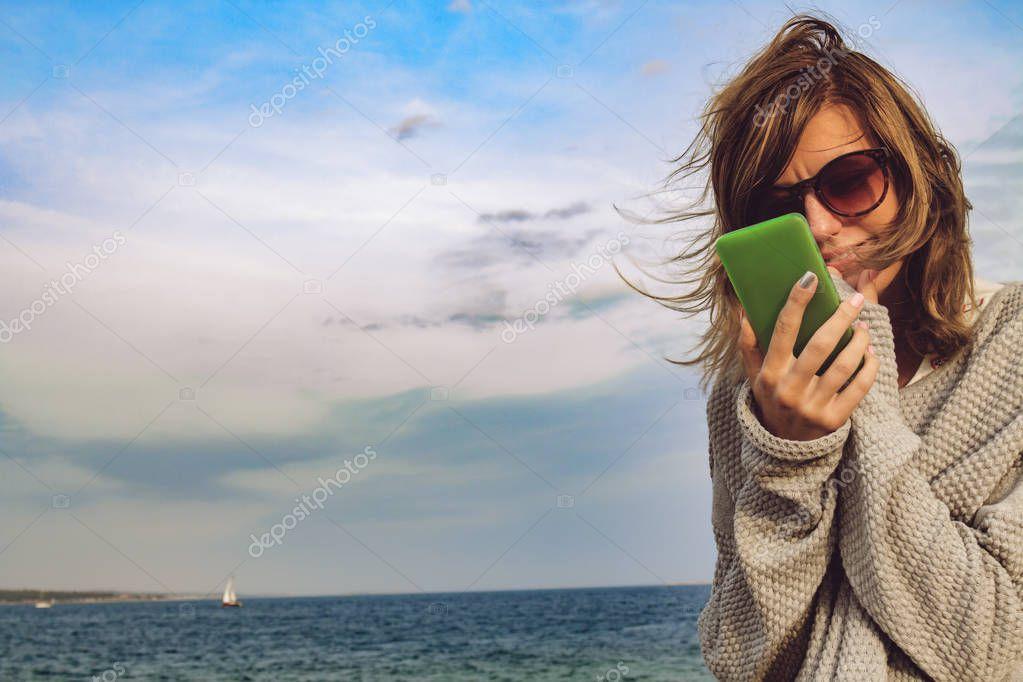 Cute girl using cellphone on the ocean shore.