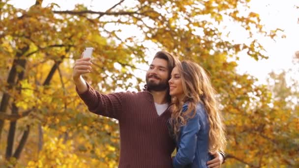 Young couple dating in autumnal park, using smartphone.