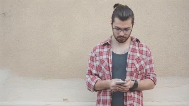 Mladý vousatý muž v brýle textových zpráv přátelům pomocí smartphonu