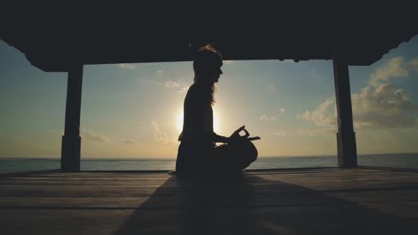 Yong žena cvičí jógu u moře