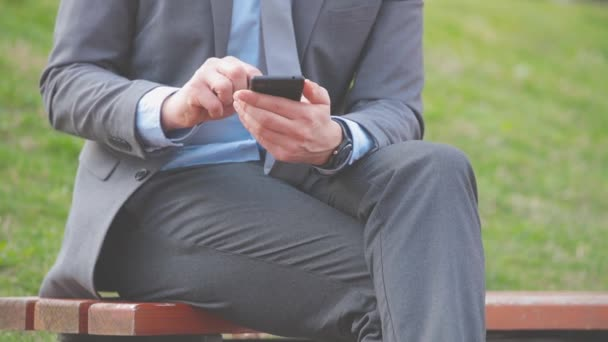 Businessman using smartphone sitting on bench outdoor