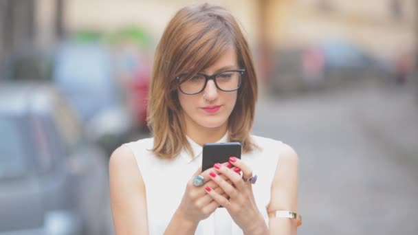 Woman in white blouse using smartphone on blurred urban background