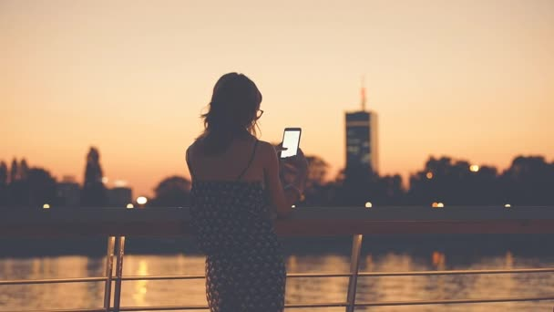 Woman in glasses using smartphone at riverside on blurred urban background