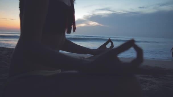 Yong woman practicing yoga at seaside