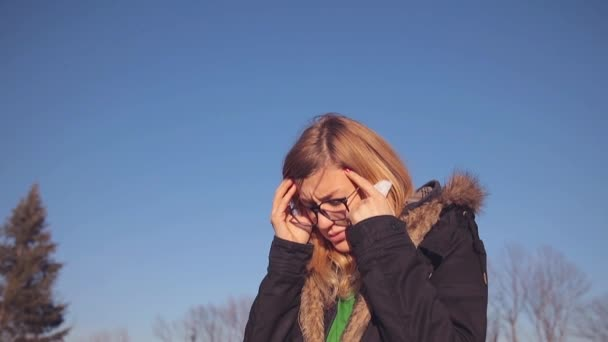 Young woman in glasses feeling headache and sneezing in park.