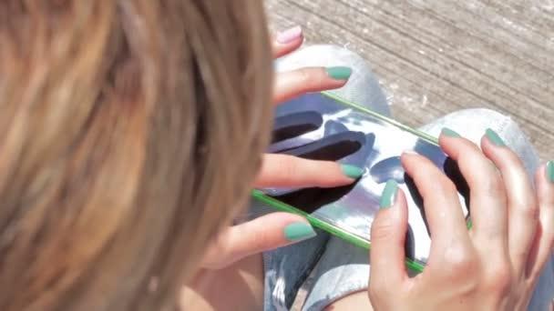 Ritagliate la vista di mani femminili facendo uso di smartphone