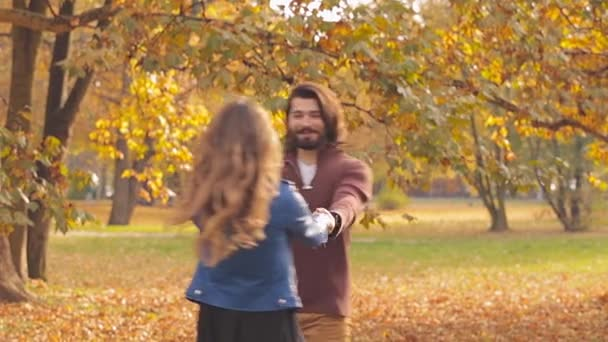 Young couple dating in autumnal park spinning around