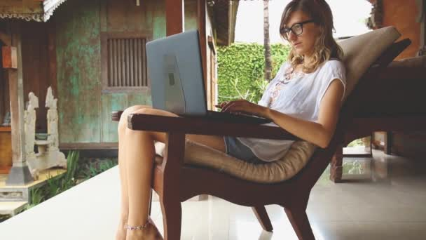 Young woman working using laptop in yard