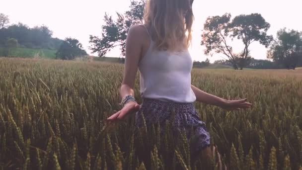 junge Frau läuft auf Feld zwischen reifem Weizen