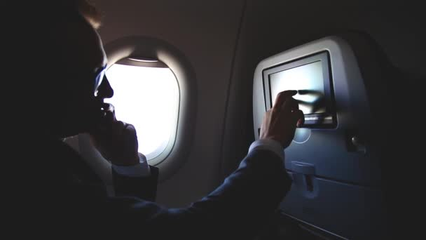 Man using smartphone and digital tablet travelling by airplane
