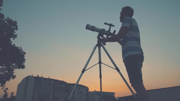 Young man adjusting and looking through astronomical telescope in evening.