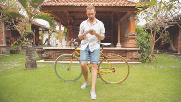 Young man using smartphone in asian yard standing near bicycle