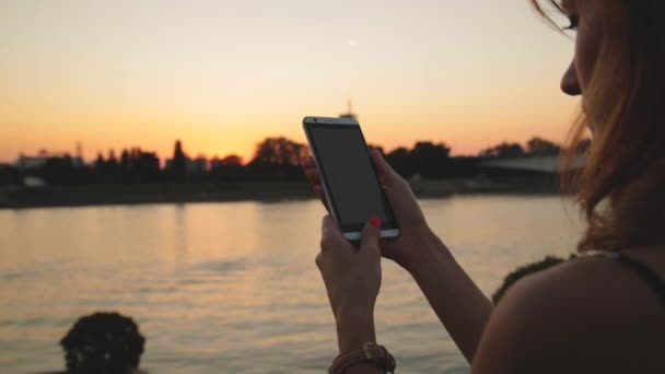 Young woman using smartphone outdoor, bridge across river on background.