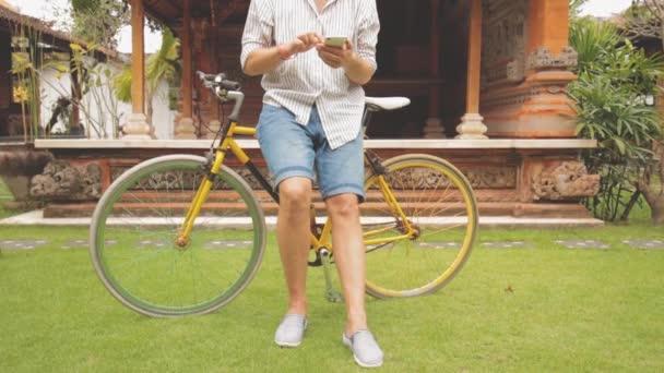Fiatal ember használ smartphone az ázsiai udvarban áll közel kerékpár
