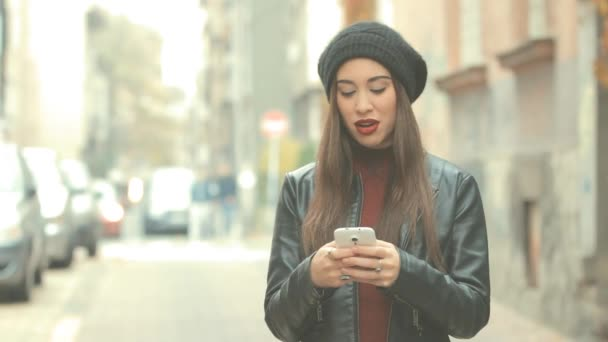 Young brunette woman with red lipstick and beanie hat using smartphone on blurred city background
