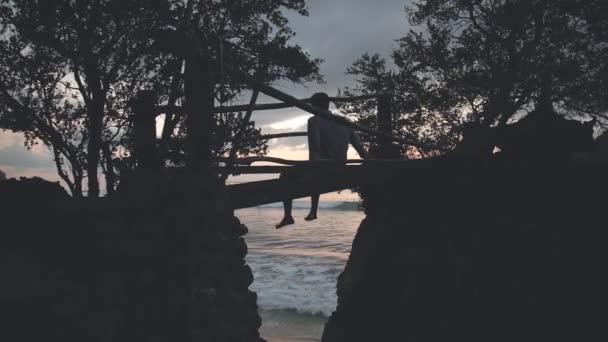 Man sitting on bridge looking at sea