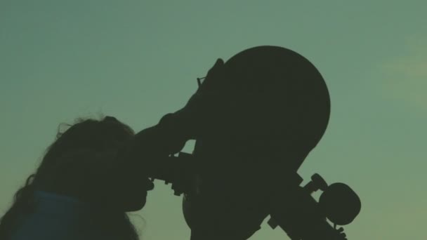 Young woman looking through astronomical telescope in evening.