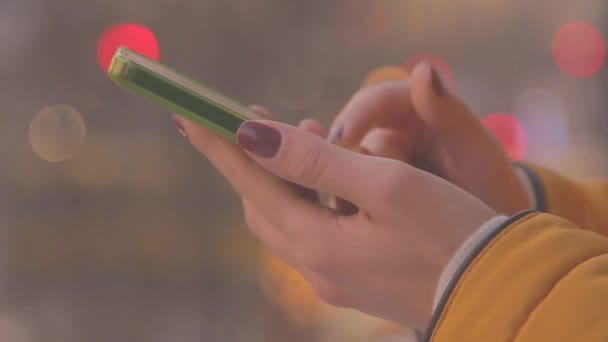 Female hands using smartphone on blurred city background