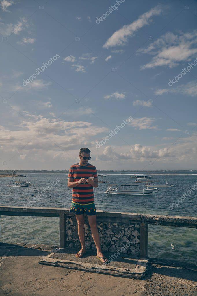 Man using cellphone on the ocean beach.