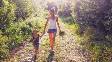 Mother and son picking flowers / herbs in nature.