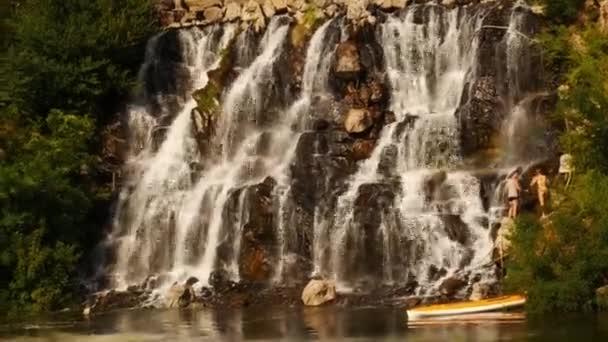 Turisté se dostali z kajaku a šplhali do skal nedaleko krásného vodopádu.