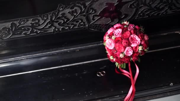 A beautiful wedding bouquet of red roses and pink peonies lies on the piano with gold rings