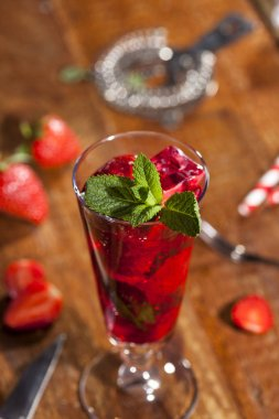 Summer cold drink with strawberries, mint and ice in glass on wooden background. Closeup of cocktails with fresh berry fruits.