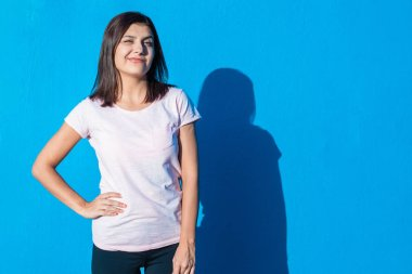 Beautiful cheerful young girl wearing casual clothes standing isolated over blue background on a sunny day. Woman feels good and full of energy. People and emotions image concept with copy space.