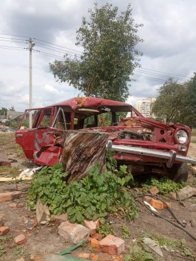 old broken red car, crashed and abandoned car after an accident, rusty car