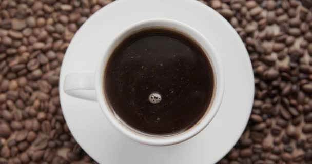 Top view of a cup of hot coffee on a dark background full of coffee beans. 4K shot