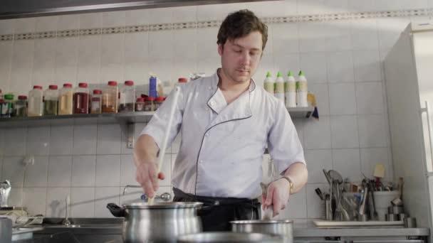 Šéf vaří v kuchyni v restauraci. Fešák vaří polévku v kuchyni. Kavkazský kuchař pracující v kuchyni restaurace.