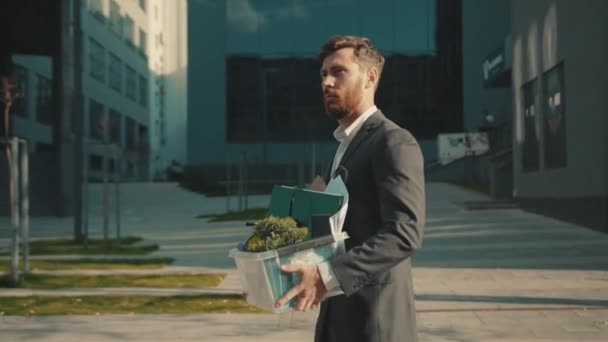 Attractive office worker man walking with box of personal stuff lose a job got fired due to a coronavirus crisis unemployed depression business corporate employment economy outdoors slow motion