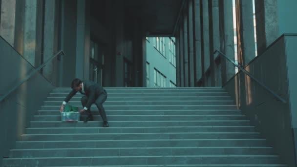 Empörter junger Mann sitzt auf der Treppe Kopf weg mit Kiste voller persönlicher Dinge verlieren einen Job wurde aufgrund einer Coronavirus-Krise entlassen Arbeitslosigkeit Depression Unternehmen Beschäftigung Wirtschaft Zeitlupe