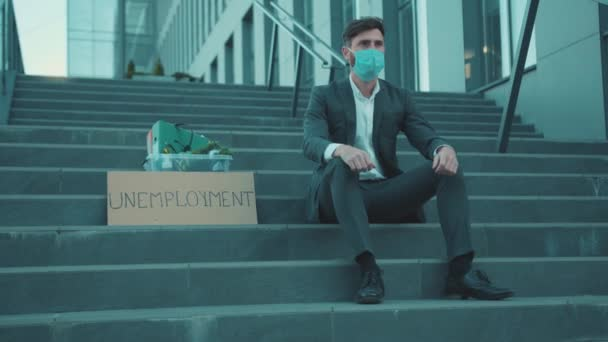Serious man wear mask sitting on stairs head off with box personal stuff and poster with the inscription Unemployment got fired due to coronavirus crisis depression corporate economy slow motion