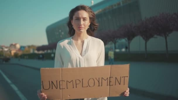 Serious young caucasian woman protests against unemployment holding a strike banner standing outside business building. Crisis 2020. Job loss during quarantine.