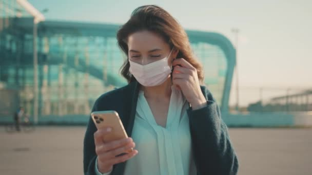 Coronavirus. Quarantine is over. Happy young woman reading hopeful news on smartphone feel relieved of pandemic ending. New life. Changes concept.