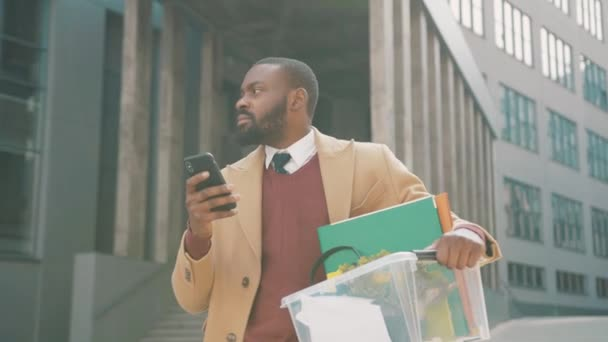 African american man use phone stand with box of personal stuff lose a job got fired due to a coronavirus crisis unemployed employment economy slow motion