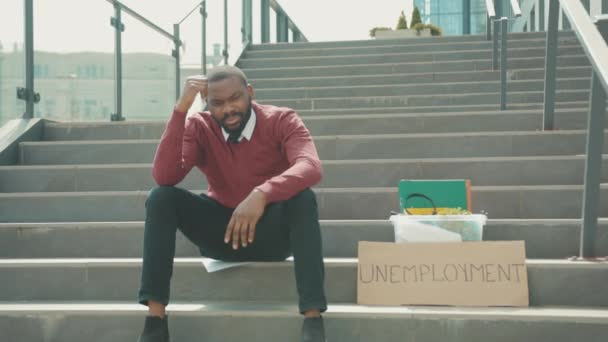 African american young man sitting on stairs use phone with box personal stuff and poster with the inscription Unemployment got fired due to coronavirus crisis depression economy slow motion