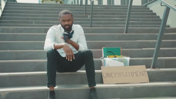 Worried African american young man sitting on stairs with box personal stuff and poster with the inscription Unemployment got fired due to coronavirus crisis depression economy slow motion