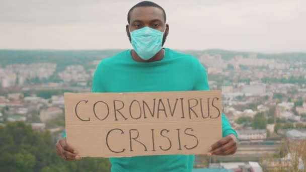 Fired african american director businessman standing on mountain showing invocatory banner Coronavirus crisis fighting for employment. Pandemic. Global problems.