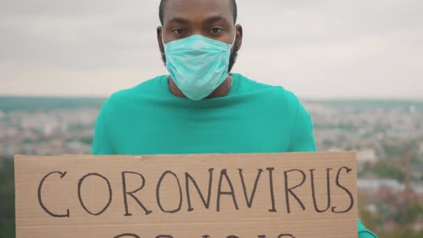 Black activist in face protective mask holding Coronavirus Crisis cardboard banner standing on the mountain. Outdoor portrait. Pandemic. Unemployment. Problems.