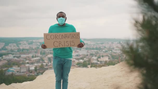 Unemployed afro-american man holding invocatory banner saying Coronavirus Crisis fight for democracy on mountain top. Cityscape. Quarantine. Pandemic.