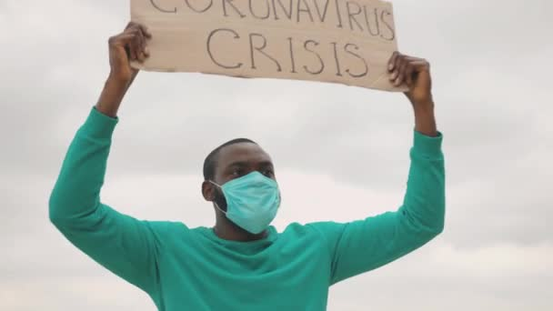 Portrait persistent young black man wearing face mask and striking with banner for employment. Job loss. Coronavirus Crisis. Pandemic in Europe. Quarantine.