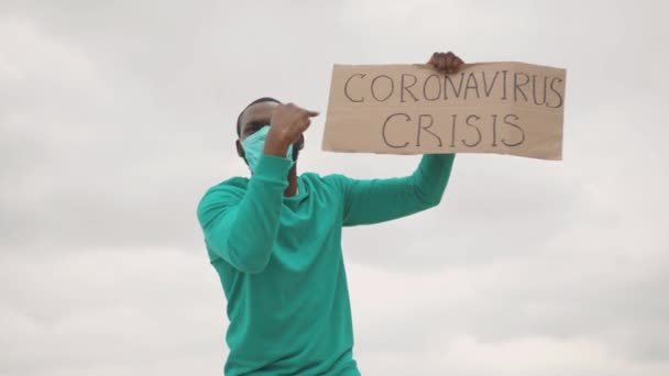 Furious strong afro-american activist in face mask striking against financial crisis 2020 during coronavirus quarantine. Pandemic. Global unemployment.