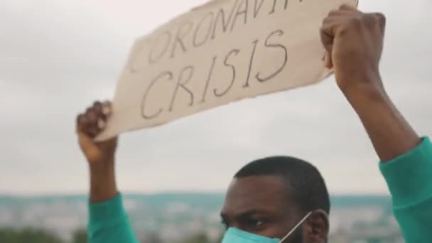 Angry strong african unemployed man fighting against job loss showing Coronavirus Crisis banner shouting call outs on mountain top. Pandemic. Glonal unemployment.