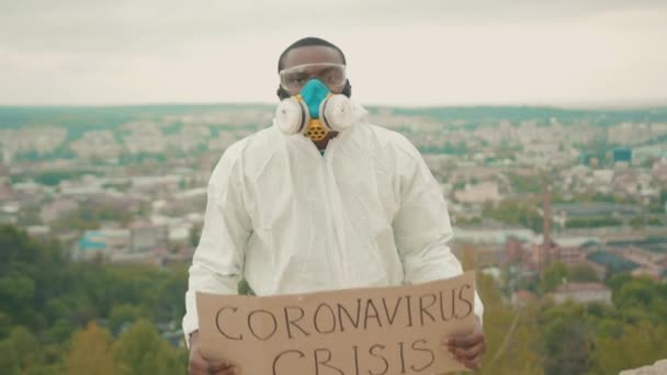 NEW YORK - March, 28, 2020: Fired afro-american scientist in full white protection hazmat showing invocatory crisis banner on mountain top. World unemployment. Job loss. Pandemic. Quarantine.