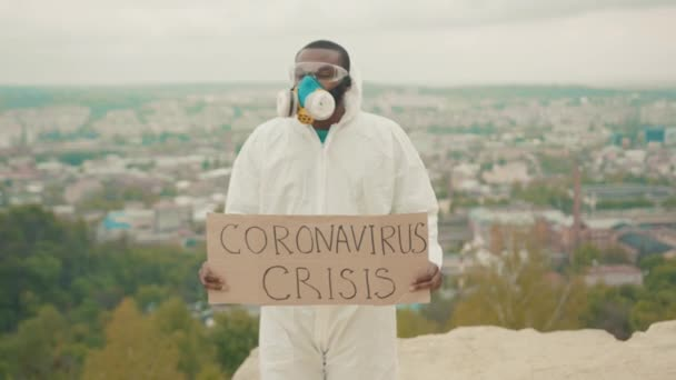 Fired businessman in full body hazmat protective suit respirator showing crisis banner at camera striking on mountain top. Unemployment due to quarantine.