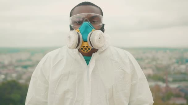 Young african man in white hazmat overall respirator facial mask strike for employment on mountain top. Jobless citizen. Global crisis 2020. Coronavirus outbreak.