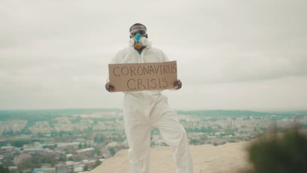 Strong male activist in respirator full body hazmat white protection suit showing Coronavirus Crisis banner outside. Job loss. Global unemployment. Pandemic.